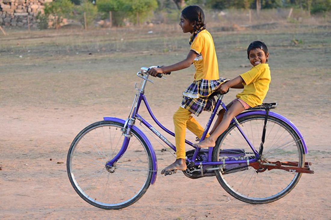 Un par de niñas juegan con una bicicleta en la ciudad india de Orchha | Foto © Ignasi Rovira