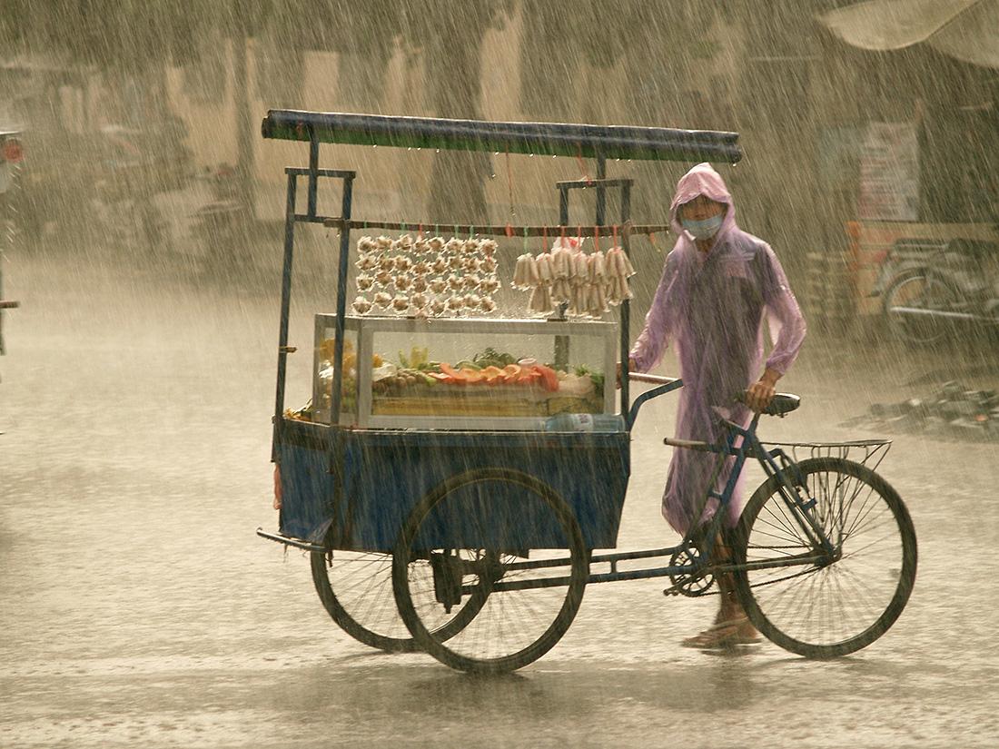 Un vendedor aguanta el chaparrón en Camboya | Foto © Albert Roset